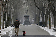 A man walks his dog down Commonwealth Avenue as Winter Storm Nemo begins to drop snow in Boston, Massachusetts, U.S., on Friday, Feb. 8, 2013. The storm is expected to dump upwards of 2 feet of snow on the region overnight. Photographer: Kelvin Ma/Bloomberg