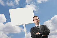 Confident businessman with arms crossed standing by blank sign against cloudy sky
