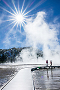 People wander through geothermal steam on the Grand Prismatic Spring boardwalk, under a sunburst. Yellowstone National Park, Wyoming, USA.