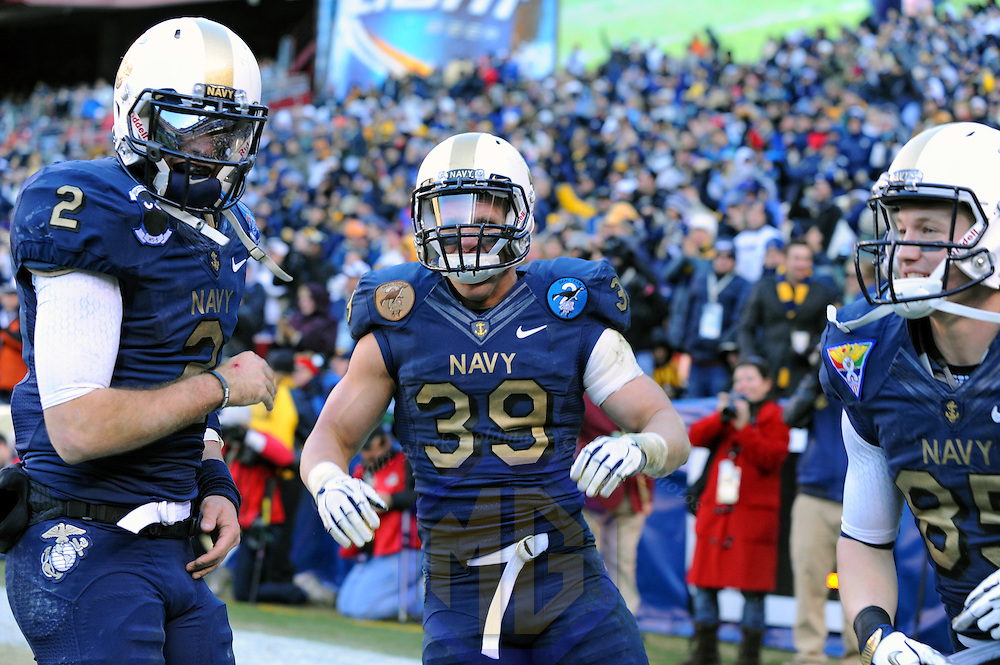 10 December 2011:   Navy Midshipmen fullback Alexander Teich (39) celebrates his touchdown with quarterback Kriss Proctor (2) and wide receiver Matt Aiken (85) in action against the Army Black Knights at Fed Ex field in Landover, Md. in the 112th annual Army Navy game where Navy defeated Army, 27-21 for the 10th consecutive time.