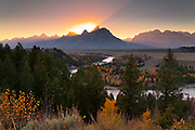 The setting sun ignites a cloudless sky, casting a warm glow over the Snake River in Grand Teton National Park