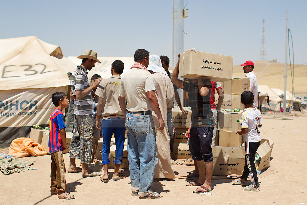 © Licensed to London News Pictures. 27/07/2014. Erbil, Iraq. Refugees from southern Iraq receive supplies at a camp for internally displaced persons (IDP's) at the Kalak Checkpoint near Erbil in Iraqi-Kurdistan. © Licensed to London News Pictures.