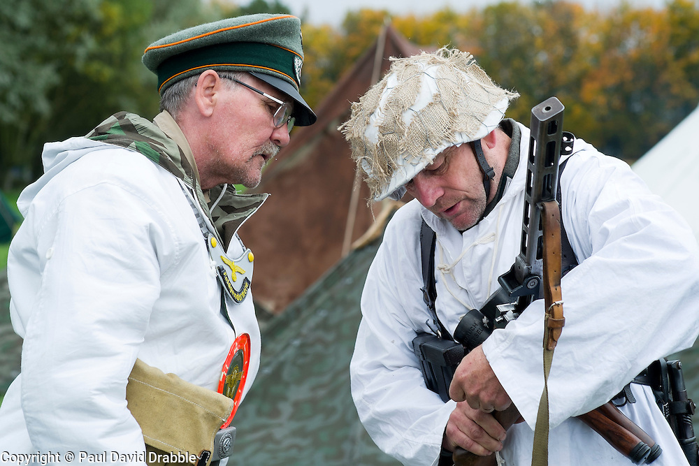 Re-enactors portraying German troops operating on the Russian Front examins a soviet PPS41 Sub machine gun. On the left is a  feldgendarme (field Policeman). He can be identified by the Orange trim or Waffenfarbe seen on his hat and the Goget around his neck. both are wearing white winter camouflage which is reversible to splinter pattern camouflage.<br />