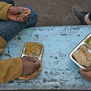 Two men having a Chhole Batora lunch on the street in Raipur, Chhattisgarh, January 2007