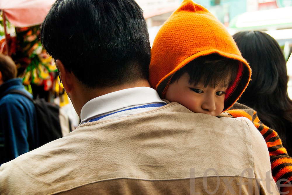 A child with a bright orange hooded jumper is carried by his father through a street-market in La Paz, Bolivia ***NOTE: Image may be available for limited editorial licensing only. For all licensing queries please contact us.***