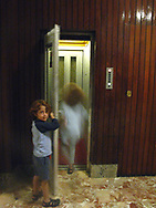 A young boy opens the elevator door for his sister in an apartment building in central Torino, Italy.