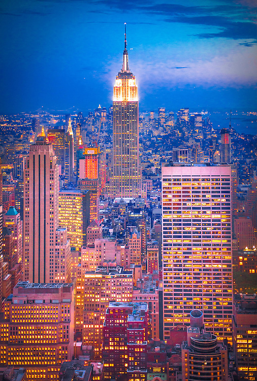 The glowing New York City skyline at dusk, seen from the Top of the Rock observations deck in Rockefeller Center's RCA (now Comcast) Building, aka 30 Rock, looking south toward Midtown, the Empire State Building and Lower Manhattan