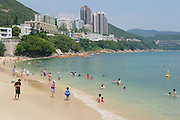 HONG KONG, CHINA - SEPTEMBER 16, 2012: Unidentified tourists sunbathe at the Stanley town beach in Hong Kong, China. Stanley town is a tourist attraction in Hong Kong.