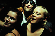 Two women and gurning man wearing fishing hat and circular sunglasses, Queen Club, Paris, France, 2001.