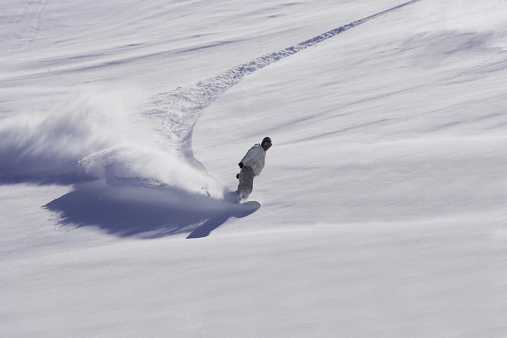 Female snowboarder turns in fresh powder snow Serre Chevalier, France