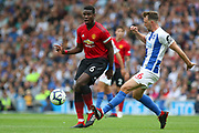 Manchester United Midfielder Paul Pogba tackles Brighton and Hove Albion midfielder Dale Stephens (6) during the Premier League match between Brighton and Hove Albion and Manchester United at the American Express Community Stadium, Brighton and Hove, England on 19 August 2018.