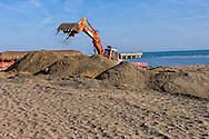 Lido di Ostia, Roma<br /> Gli stabilimenti balneari  si preparano per la stagione estiva. Una ruspa sistema la sabbia.<br /> Lido di Ostia, Rome<br /> The bathing facilities are preparing for the summer season. A bulldozer system the sand.