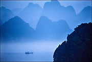 On the tranquil waters of Vietnam's Gulf of Tonkin, a sampan glides through Halong Bay, where limestone cliff s and rocky outcroppings covered in tropical hardwoods disappear into the fog. A UNESCO World Heritage site, Halong Bay today is overwhelmed with tourists arriving in buses, sailboats, and cruise ships. © Steve Raymer/National Geographic Creative