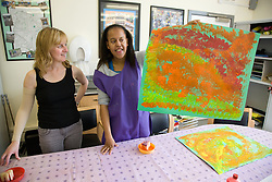 Day Service user with learning disability holding up her painting looked on by Day Service Officer,