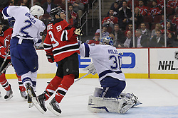 Feb 9; Newark, NJ, USA; New Jersey Devils left wing Zach Parise (9) gets hit with a shot in the back, while Tampa Bay Lightning goalie Dwayne Roloson (30) looks for the loose puck during the first period at the Prudential Center.