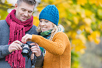 Portrait of mature couple looking pictures on camera in park