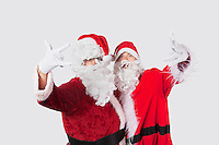 Portrait of young men in Santa costume gesturing over gray background