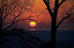 Sun setting over frozen Lake Michigan with trees in foreground