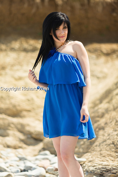 Young woman wearing a short floaty, blue dress on  a sunny day.