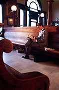 Businessman in gray suit reads financial newspaper while waiting for train in railway terminal waiting room.
