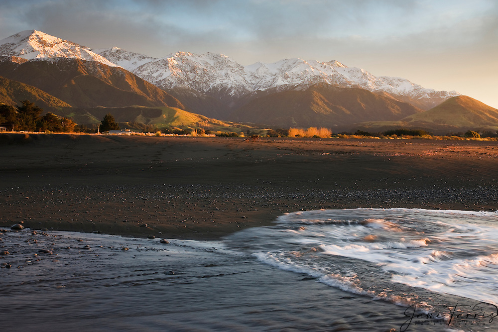 Waves cover a black sand beach in front of snow covered mountain peaks of New Zealand's South Island at sunset, South Island,New Zealand