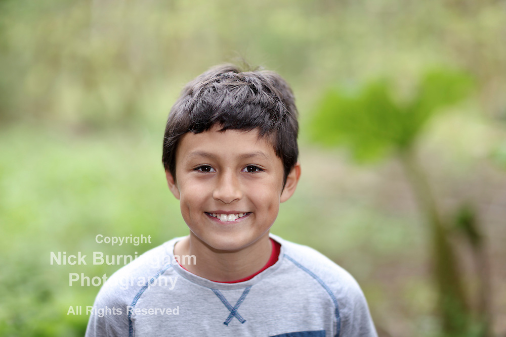 Young smiling mixed race boy in woods - shallow depth of field