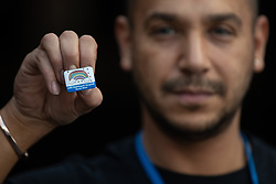 """© Licensed to London News Pictures . 22/04/2020. Manchester, UK. In an echo of Health Secretary Matt Hancock's pose with a """"CARE"""" badge , Porter DANIEL TODD (35) , holds a commemorative badge , being given as a gift to those who have worked at the NHS Nightingale Hospital in Manchester . The National Health Service has built a 648 bed field hospital for the treatment of Covid-19 patients , at the historical railway station terminus which now forms the main hall of the Manchester Central Convention Centre . The facility is treating patients from across the North West of England , providing them with general medical care and oxygen therapy after discharge from Intensive Care Units . Photo credit : Joel Goodman/LNP"""