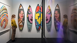 © Licensed to London News Pictures. 21/01/2020. LONDON, UK. A staff member views decorated fibreglass surfboards by Andy Warhol. Preview of London Art Fair at the Business Design Centre in Islington.  Over 100 galleries are offering works, including museum-quality modern and contemporary art from internationally renowned artists and emerging artist, to collectors in a show which runs 22-26 January 2020.  Photo credit: Stephen Chung/LNP