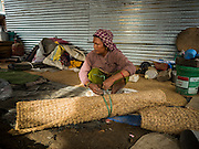 02 AUGUST 2015 - BHAKTAPUR, NEPAL:  A woman rolls up her sleeping mat in her shelter in a small Internal Displaced Person (IDP) camp at Durbar Square in Bhaktapur for people left homeless by the Nepal earthquake. The Nepal Earthquake on April 25, 2015, (also known as the Gorkha earthquake) killed more than 9,000 people and injured more than 23,000. It had a magnitude of 7.8. The epicenter was east of the district of Lamjung, and its hypocenter was at a depth of approximately 15km (9.3mi). It was the worst natural disaster to strike Nepal since the 1934 Nepal–Bihar earthquake. The earthquake triggered an avalanche on Mount Everest, killing at least 19. The earthquake also set off an avalanche in the Langtang valley, where 250 people were reported missing. Hundreds of thousands of people were made homeless with entire villages flattened across many districts of the country. Centuries-old buildings were destroyed at UNESCO World Heritage sites in the Kathmandu Valley, including some at the Kathmandu Durbar Square, the Patan Durbar Squar, the Bhaktapur Durbar Square, the Changu Narayan Temple and the Swayambhunath Stupa. Geophysicists and other experts had warned for decades that Nepal was vulnerable to a deadly earthquake, particularly because of its geology, urbanization, and architecture.      PHOTO BY JACK KURTZ