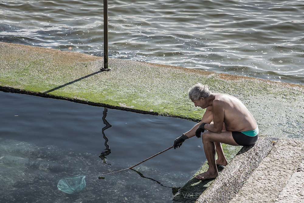 a man on the edge of a natural sea-water pool in Cascais, tries to catch crabs with a net.