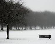 A snow covered bench sits empty in Jesus Green, Cambridge, United Kingdom.