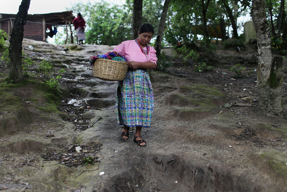 Plan de Sanchez massacre survivor Faustina Cojom Manuel walks out of her home carrying a basket with two turkeys that she will attempt to sell in Rabinal town in order to acquire some income. On July 18, 1982, Guatemalan soldiers and members of the right-wing paramilitary Civil Self-Defense Patrols (Patrullas de Autodefensa Civil, or PACs) brutally massacred 268 people in Plan de Sanchez, a remote Achi Mayan hamlet near Rabinal town. The event occurred during the scorched earth campaigns carried out by the de facto government of general Efraín Ríos Montt. On March 21, 2012, five former members of the PACs were each sentenced to 7710 years in prison for their participation in the massacre. Plan de Sánchez Hamlet, Rabinal, Baja Verapaz, Guatemala. July 21, 2012.