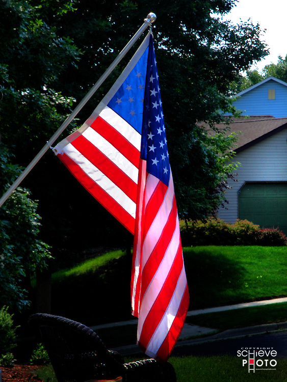 Fourth of July American flag hangs from a house.