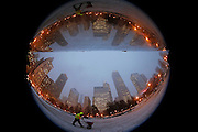 "A worker is reflected in the mirrored sculpture ""Cloud Gate"" as he sprinkles de-icing salt around the bean-shaped sculpture in Chicago, Illinois, December 16, 2013.  Picture taken with a fish-eye lens.  REUTERS/Jim Young"