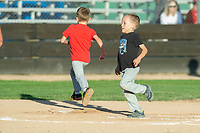 KELOWNA, BC - JULY 17: Twins finish racing the bases against each other at Elks Stadium on July 17, 2019 in Kelowna, Canada. (Photo by Marissa Baecker/Shoot the Breeze)