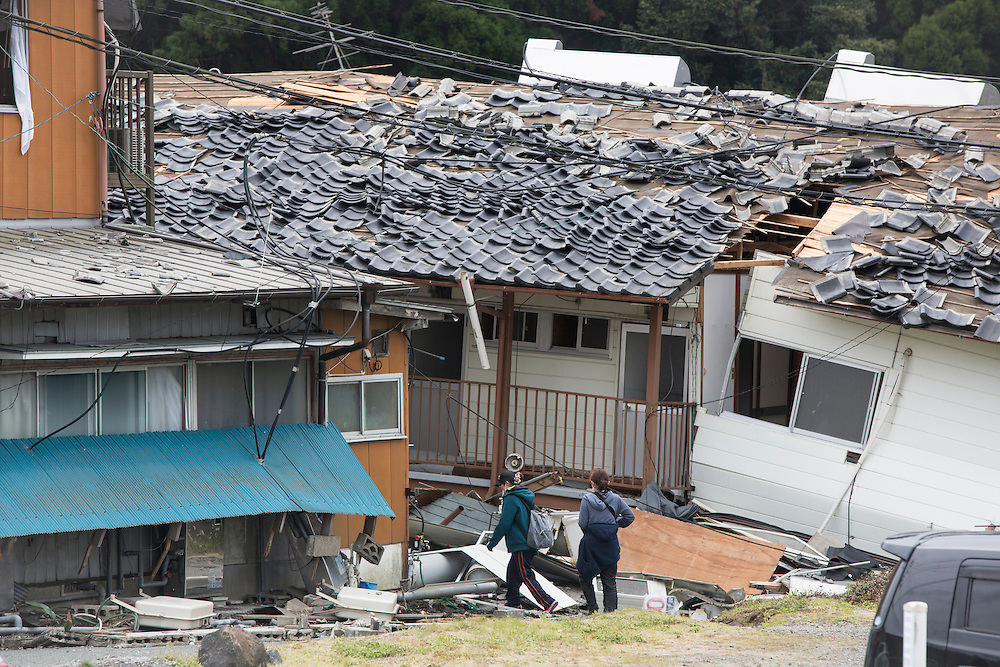 KUMAMOTO, JAPAN - APRIL 18: A resident come back home as they pass thru a collapsed house after an earthquake on April 18, 2016 in Mashiki, Kumamoto, Japan. At least nine people have died in a powerful earthquake, with a preliminary magnitude of 6.4, and followed by magnitude 7.3 quake that struck Kumamoto Prefecture yesterday.<br /> <br /> Photo: Richard Atrero de Guzman
