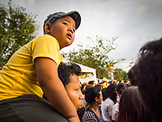 02 DECEMBER 2014 - BANGKOK, THAILAND: A man and his son watch the Trooping of the Colors parade on Sanam Luang in Bangkok. The Thai Royal Guards parade, also known as Trooping of the Colors, occurs every December 2 in celebration of the birthday of Bhumibol Adulyadej, the King of Thailand. The Royal Guards of the Royal Thai Armed Forces perform a military parade and pledge loyalty to the monarch. Historically, the venue has been the Royal Plaza in front of the Dusit Palace and the Ananta Samakhom Throne Hall. This year it was held on Sanam Luang in front of the Grand Palace.    PHOTO BY JACK KURTZ