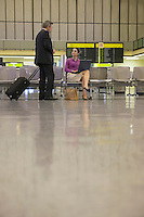 Business woman using laptop with business man approaching her in airport lobby