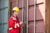 Male worker inspecting cargo container while writing on clipboard in shipping yard