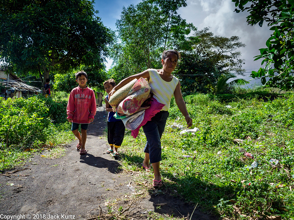 "22 JANUARY 2018 - CAMALIG, ALBAY, PHILIPPINES: A family carries their belongings to a waiting government truck after they were told they had to evacuate their home because of its proximity to the Mayon volcano. There were a series of eruptions on the Mayon volcano near Legazpi Monday. The eruptions started Sunday night and continued through the day. At about midday the volcano sent a plume of ash and smoke towering over Camalig, the largest municipality near the volcano. The Philippine Institute of Volcanology and Seismology (PHIVOLCS) extended the six kilometer danger zone to eight kilometers and raised the alert level from three to four. This is the first time the alert level has been at four since 2009. A level four alert means a ""Hazardous Eruption is Imminent"" and there is ""intense unrest"" in the volcano. The Mayon volcano is the most active volcano in the Philippines. Sunday and Monday's eruptions caused ash falls in several communities but there were no known injuries.    PHOTO BY JACK KURTZ"