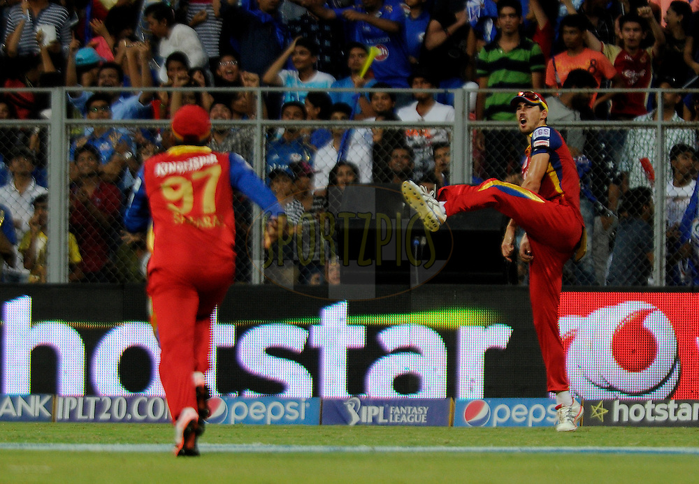 Mitchell Starc of Royal Challengers Bangalore celebrate the wicket of Kieron Pollard of Mumbai Indians during match 46 of the Pepsi IPL 2015 (Indian Premier League) between The Mumbai Indians and The Royal Challengers Bangalore held at the Wankhede Stadium in Mumbai, India on the 10th May 2015.<br /> <br /> Photo by:  Pal Pillai / SPORTZPICS / IPL