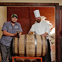 Left to Right, Front Street Brewery Head Brew Master Kevin Kozak and Front Street Brewery Chef Patrick Gaynor are seen with a barrel that once held Jim Bean Burbon. Front Street Brewery is aging beer in barrels that once held Jim Beam bourbon. Four beers have been brewed and will be paired with dishes for a special dinner Oct. 14.  Photo By Mike Spencer/STAR-NEWS