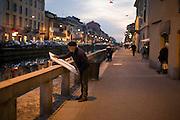 A painter gets canvas ready for a new paint outside his studio at Alzaia Naviglio Grande (canal towpath) in Milan, January, 2011. © Carlo Cerchioli..Pittore prepara la tela per un nuovo dipinto fuori dal suo studio lungo Alzaia Naviglio Grande a Milano gennaio, 2011.