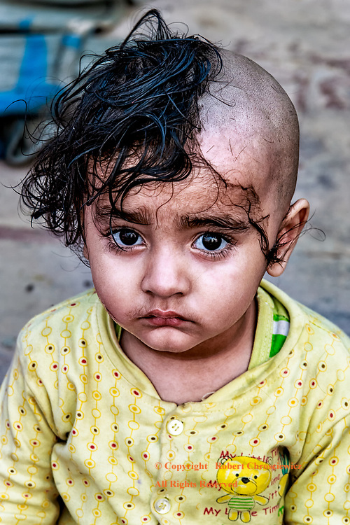 Half and Half: This sad young child is captured at the midpoint of having her hair shaved off, during the Mundan ceremony, so that she will be set  free from the bonds of her last birth, Varanasi India.