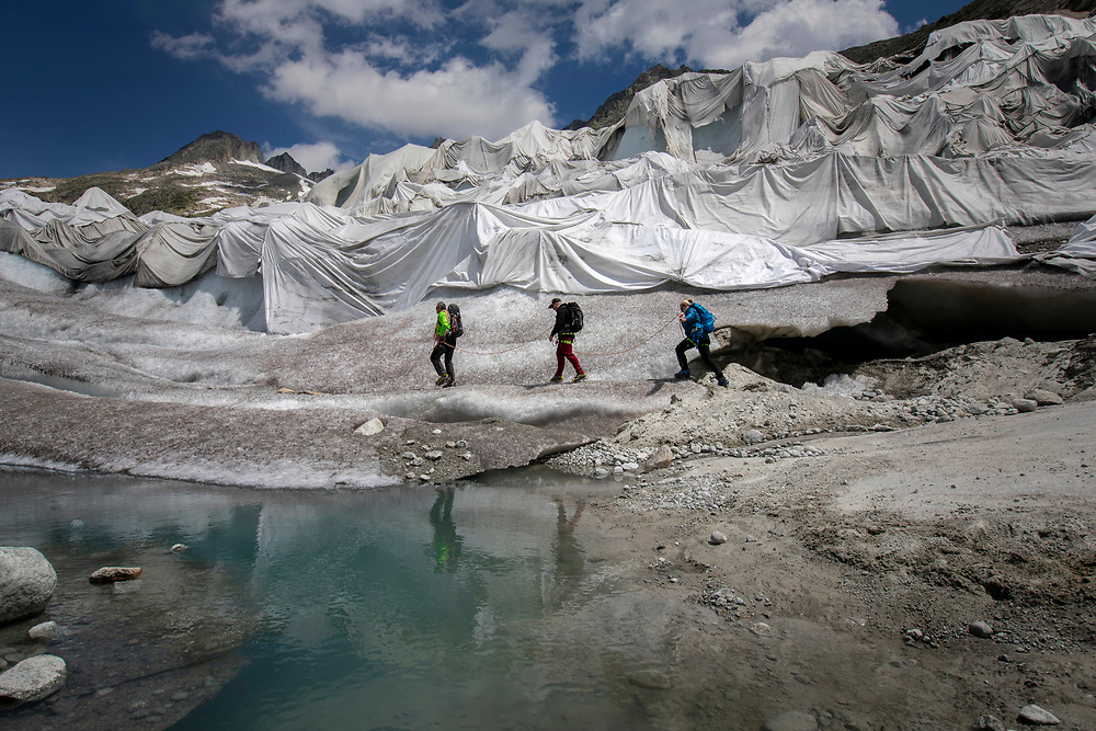 Alfredo Hoch (green jacket) and his wife Anja Behrens get ready to scale the Rhone Glacier along with their friend Ronny Miestas.. Huge fleece blankets cover parts of the Rhone Glacier in Switzerland in an attempt to stall the inevitable melting of the snow and ice. After a winter with record amounts of snow, most of it was gone when this image was taken on July 14th 2018, exposing the darker ice. While snow is a brilliant reflector of the energy from the sun, the darker ice absorbs the energy instead, accelerating the melting of the glacier. The color and darkness of glacier ice vary all over the world, depending on build-up of pollution, age of the ice, particles picked up by the ice and by microorganisms in the ice. The glacier ice is however rarely white as snow. With shorter winters and vanishing snow cover, the melting of the glaciers is accelerating.