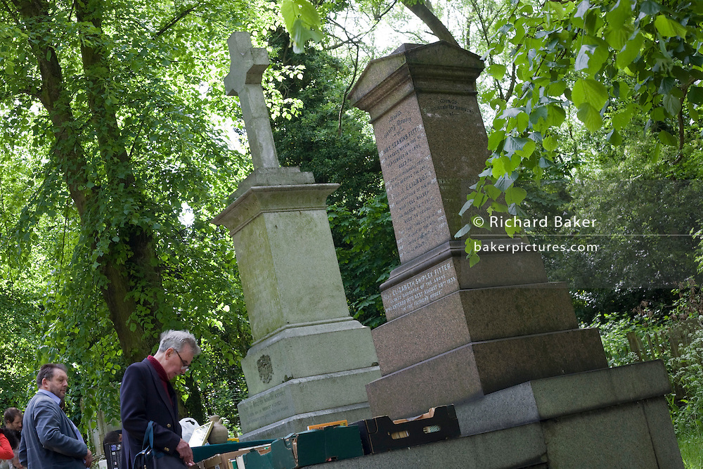 Visitors browse through a book stall beneath tombs and memorials in Nunhead Cemetery whose deceased occupants were important members of Victorian society from the industrial age. During this annual open day, it is an opportunity for the Friends of the cemetery to celebrate and educate Londoners, old and young - thereby helping to preserve and conserve this historic site.
