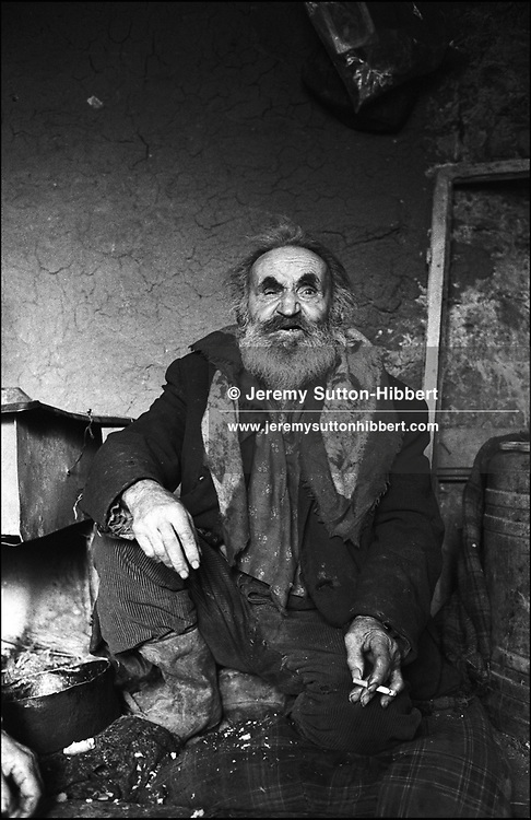 GOGU MIHAI , DEEMED UNCLEAN BY OTHER GYPSIES WHO WILL NEITHER EAT NOR DRINK WITH HIM..SINTESTI, ROMANIA. JANUARY 1994..©JEREMY SUTTON-HIBBERT 2000..TEL. +44-141-649-2912..TEL. +44-7831-138817.