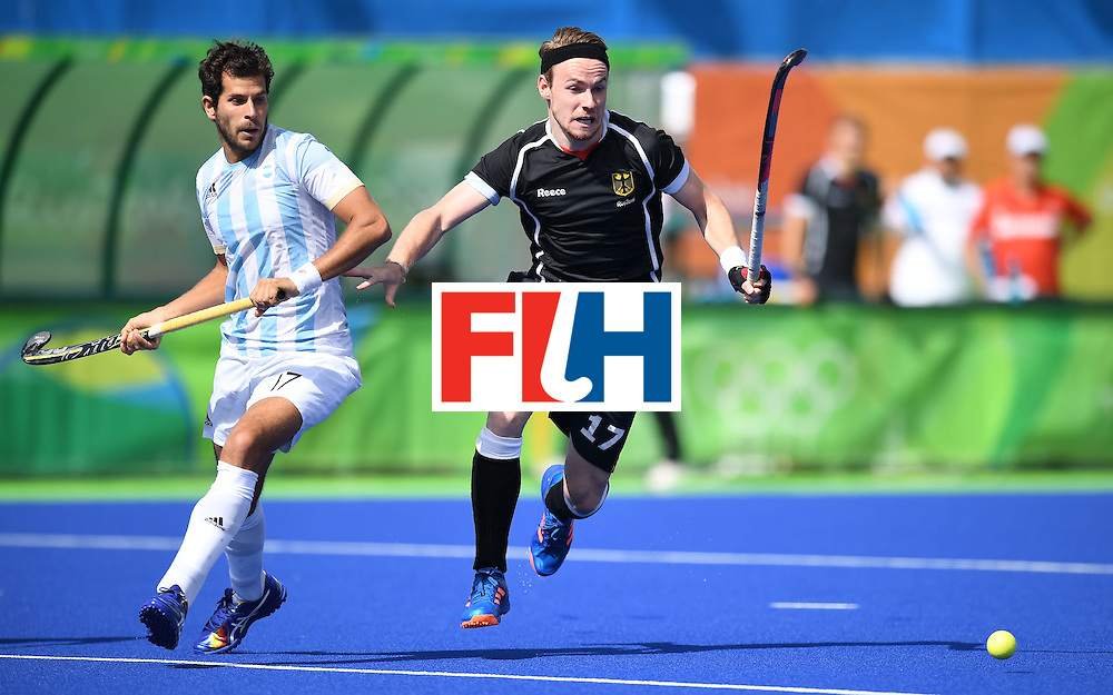 Argentina's Juan Lopez (L) and Germany's Christopher Ruhr chase the ball during the men's field hockey Argentina vs Germany match of the Rio 2016 Olympics Games at the Olympic Hockey Centre in Rio de Janeiro on August, 11 2016. / AFP / MANAN VATSYAYANA        (Photo credit should read MANAN VATSYAYANA/AFP/Getty Images)