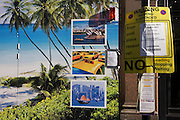 Street construction site showing tropical beach paradise and images of world cities with a London No Parking sign.