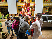 """05 SEPTEMBER 2016 - BANGKOK, THAILAND:  Men carry a statue of Ganesha into the prayer hall on the first day of Ganesha Chaturthi celebrations at Shiva Temple in Bangkok. Ganesha Chaturthi also known as Vinayaka Chaturthi, is the Hindu festival celebrated on the day of the re-birth of Lord Ganesha, the son of Shiva and Parvati. The festival, also known as Ganeshotsav (""""Festival of Ganesha"""") is observed in the Hindu calendar month of Bhaadrapada. The date usually falls between 19 August and 20 September. The festival lasts for 10 days, ending on Anant Chaturdashi. Ganesha is a widely worshipped Hindu deity and is revered by many Thai Buddhists. Ganesha is widely revered as the remover of obstacles, the patron of arts and sciences and the deva of intellect and wisdom.     PHOTO BY JACK KURTZ"""